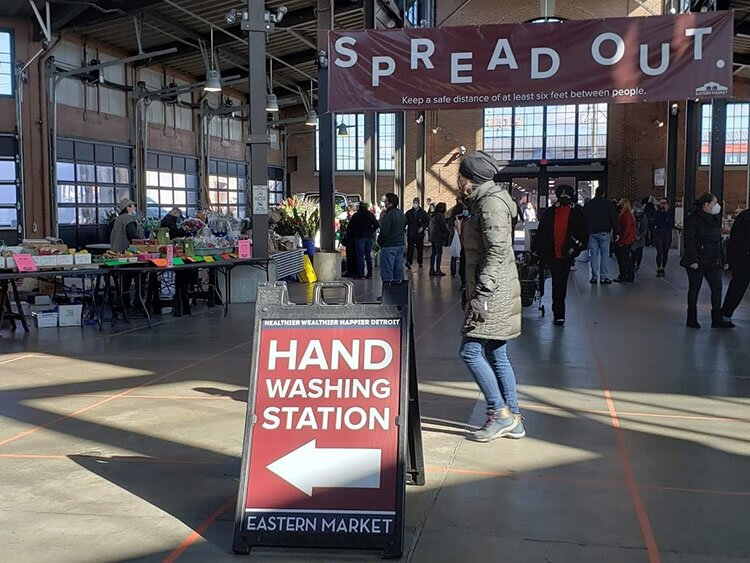 The market is visibly emptier these days, with signs indicating safety measures such as hand washing stations and signs reminding shoppers to spread out.