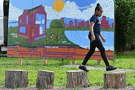 A young neighborhood resident has some fun in front of a water cycle mural at the Hamilton Rainscape Learning Lab.