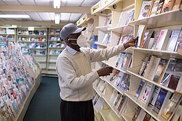 Walter Baker stocks the shelves at his Detroit shop, Baker's Bible and Bookstore.