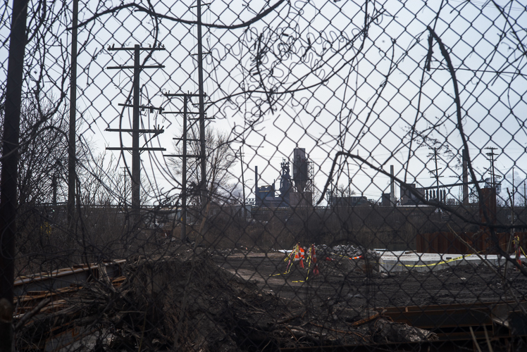 Delray's industrial landscape as seen through a fence.