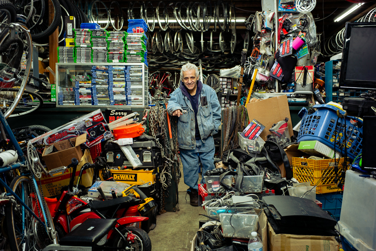 Sam Awada poses with merchandise at Livernois Bike Shop.