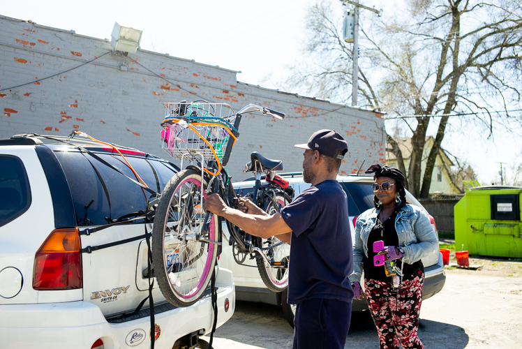 Scott Ford helps Melissa Williams mount a bike on a car.