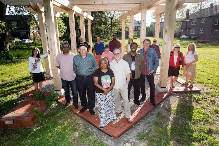Myrtle Thompson, center, Program Director and Co-Founder of Feedum Freedom, and Mikel Bresee, right center, pose with community members in front of a pavilion being built as part of the Fox Creek Artscape.