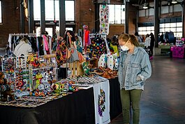 A shopper peruses local items at Eastern Market's Sunday Market earlier this year. Holiday Markets are back, with Sunday markets focusing on local vendors selling everything from beauty products to T-shirts.