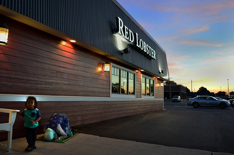 Community activist Hazel Gomez prays in front of Red Lobster, a representation of how Muslims practice their faith in America.