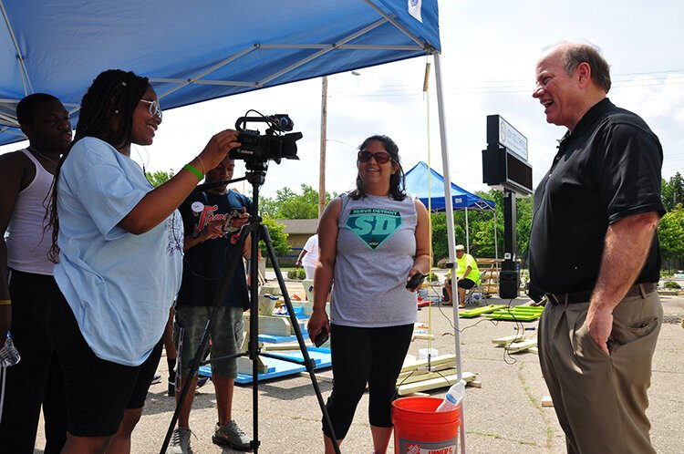 Rodney Bridges, Taylin Hodges, and Mona Ali interview Mayor Mike Duggan at a community picnic table building event.