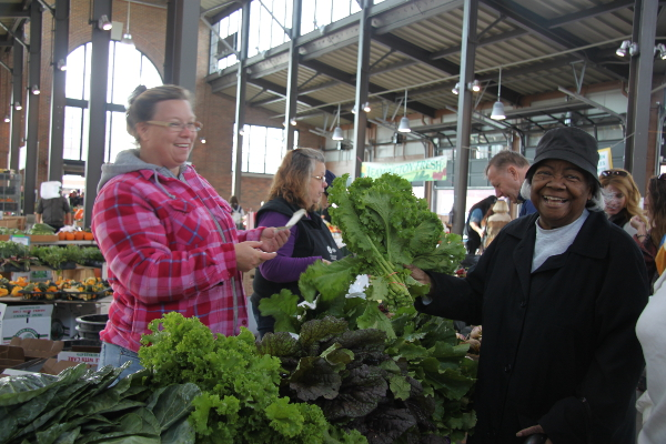 Becky of Beilait Farms hands kale to Ethel Ambrols of Brush Park Manor