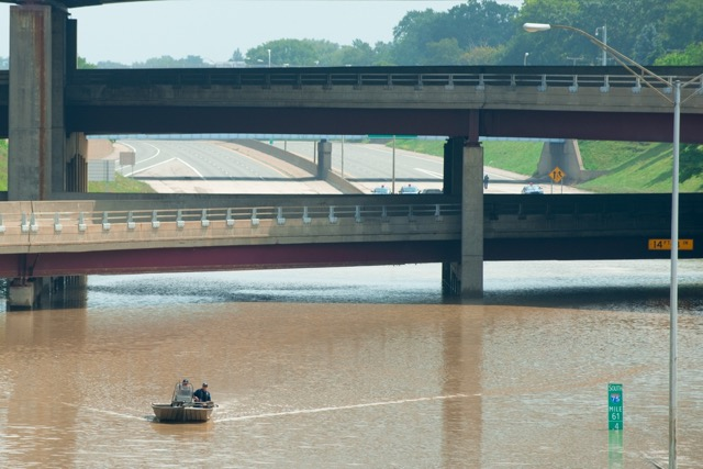 Police pilot a boat in a flooded portion of I-75 on August 12, 2014. A pumping station failed during heavy rains the night before leading to flooding.