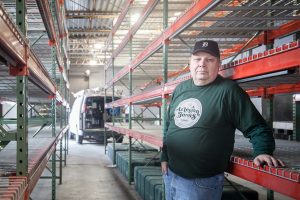 Jeff Adams stands between the growing racks at Artesian Farms