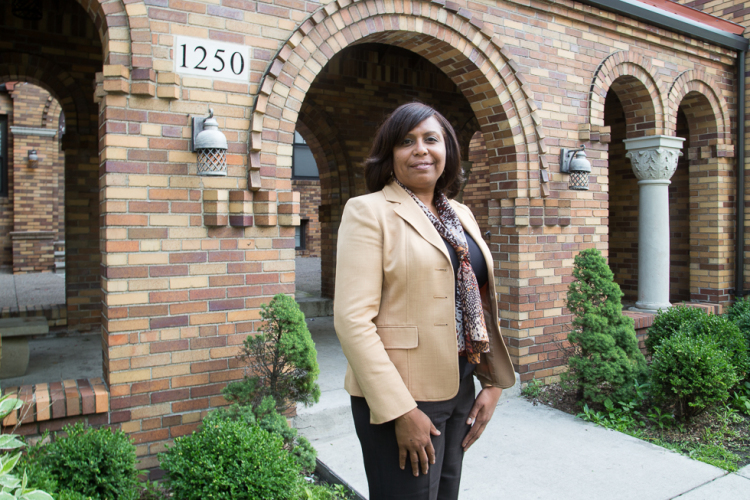 Tahirih Ziegler, executive director of Detroit LISC, in front of the Whitdel Apartments in southwest Detroit