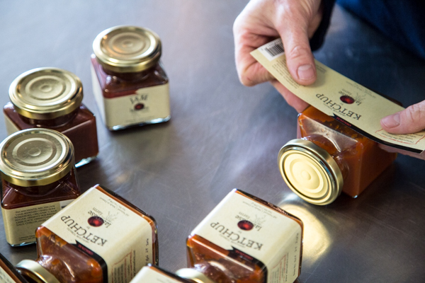 Dawn DeMuyt of Labrosse Farms labels jars of ketchup