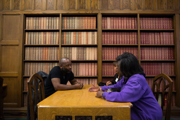 Theaster Gates converses with neighborhood residents in the library of Marygrove College