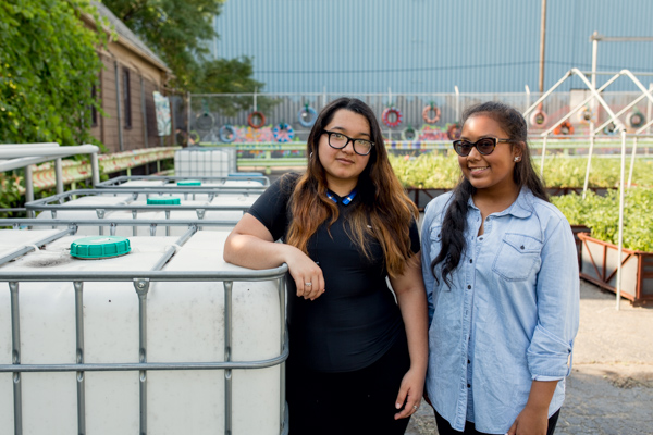 Kandis Chow and Brianna Bryant posing with the water tanks for the irrigation system The Mercy Midnight Storm is designing.