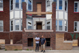 David Alade, left, and Steven Harris, right, on the steps of a building newly purchased by Harris