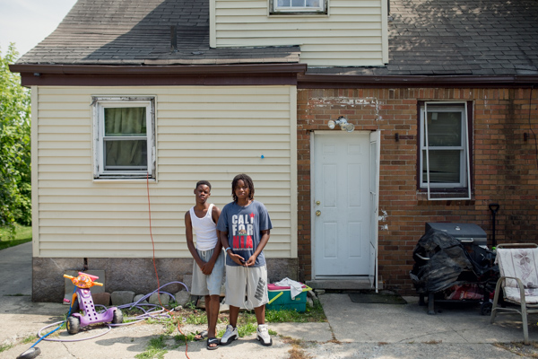 Ky'Shaun Gibson, left, with his step brother Davion Robertson, right, standing in front of the backside of Shakiya's saved home