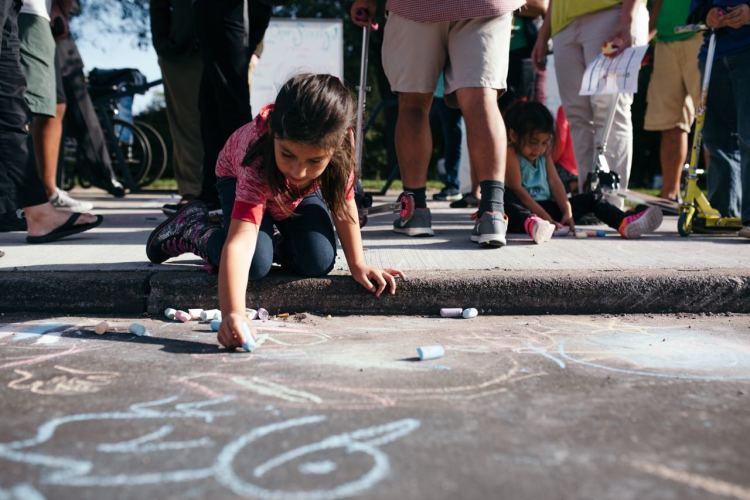 A girl writes on the street in chalk during Open Streets Detroit