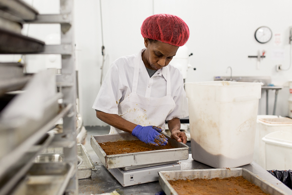 Mina Muhammad prepping crusts for magic bars. She has been working at Avalon for eight months.