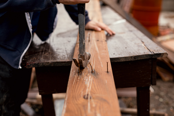 Dubay removes nails from scrapped wood, making them useable again