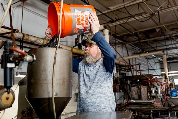 Ken Moravik, Archer Records press operator, pouring virgin vinyl in the press's hopper