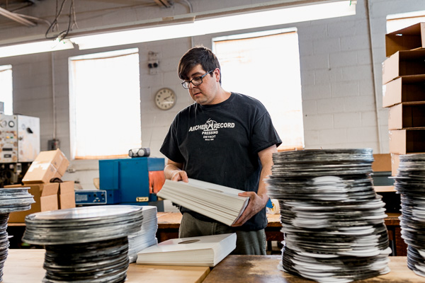 Andrew Garcia, Floor Manager at Archer Records, packaging completed records