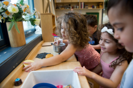 Children clean up a kitchen playset at the UM Dearborn Early Childhood Education