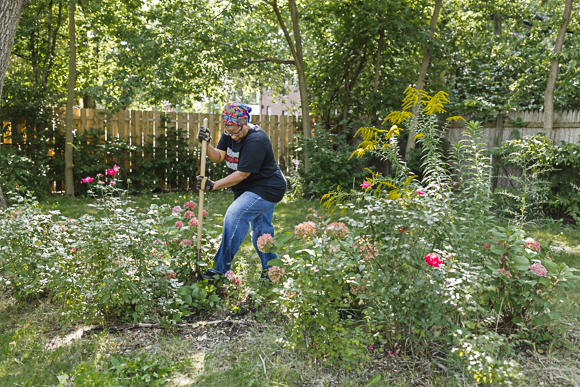 Beverly Frederick digs up weeds along Stahelin Avenue in NW Detroit