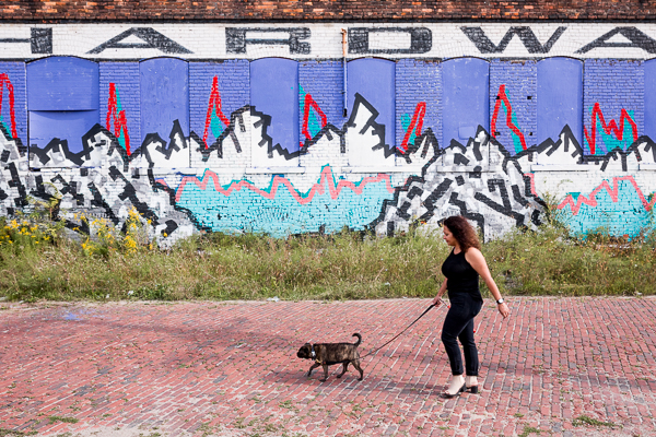 David with her dog in front of a mural