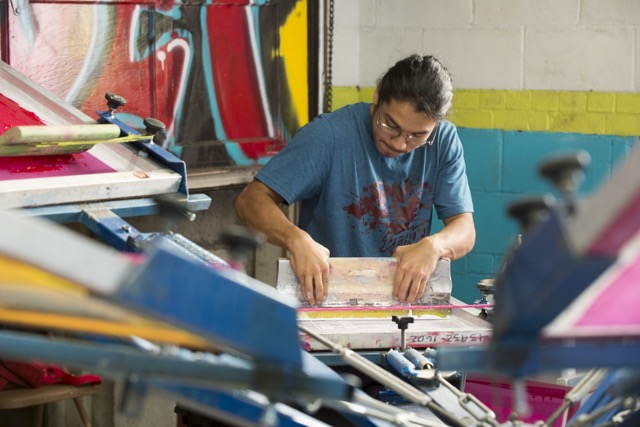 A member of Stitching Up Detroit inks a shirt at the screen printing facility at Grace in Action