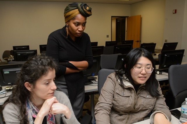 Sisters Code instructor Ronisha Harvey goes over a coding challenge with two students