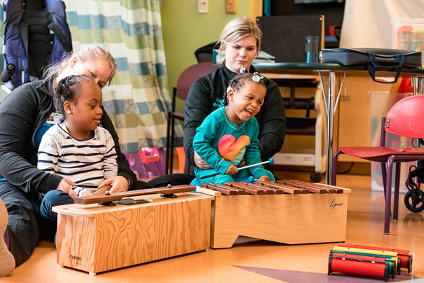 Patients Mackenzie Thomas and Darrenique Trotter play music during a therapy session