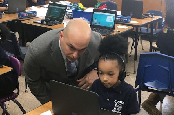 Superintendent Nikolai Vitti works with a student on a personal computer at Cooke STEM Academy