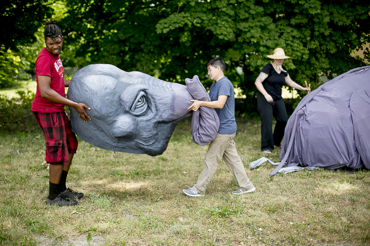 Puppeteers James Abbott and Mike Chin carry and elephant puppet created by Lindsay McCaw
