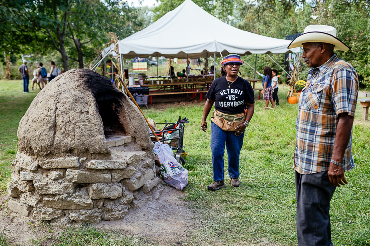 Mama Hanifa, education and outreach director of the Detroit Black Community Food Security Network, explaining the earth oven to a guest