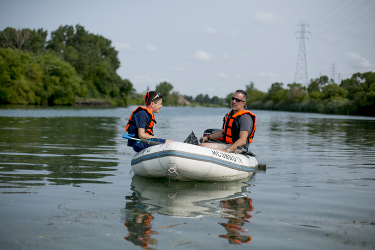 Tom and Mark travel around in their boat during a Trash Fishing outing near Zug Island