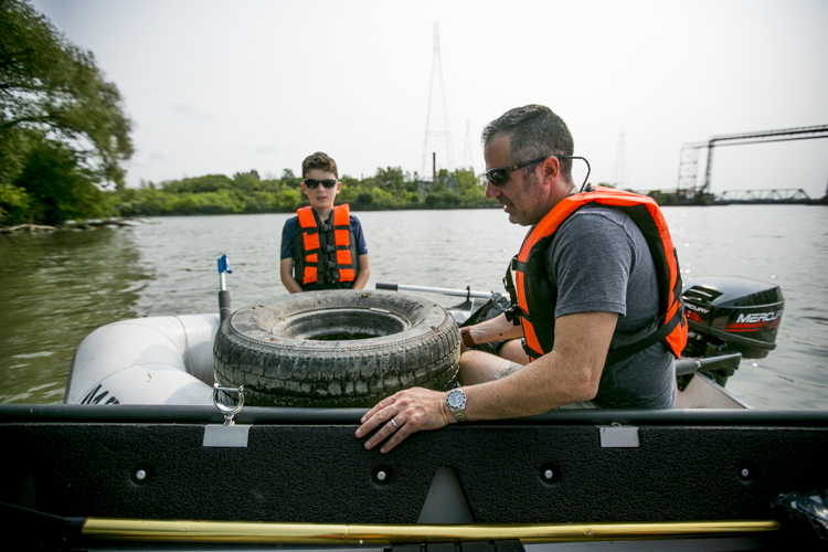 Tom and Mark pluck a tire from the water