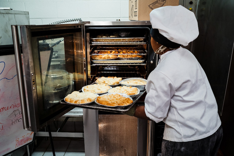 Student puts pies in the oven at Golightly's Bakeshop
