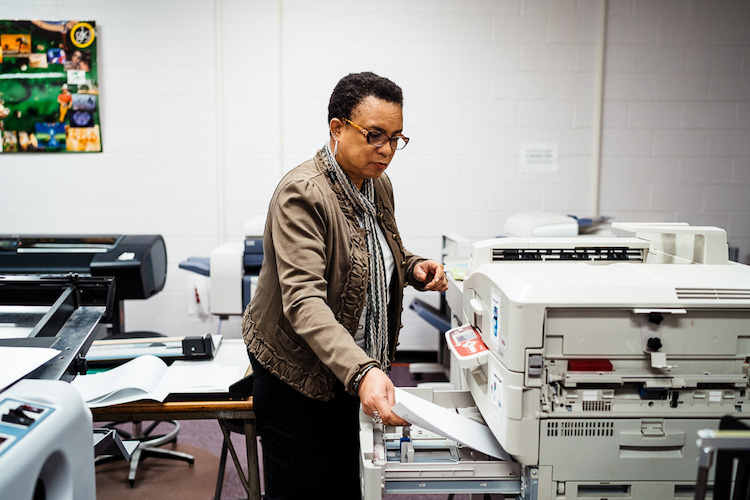 Leisia Duskin, Special Instructor for Graphics and Printing Technology classes, loading paper into the large capacity color printer