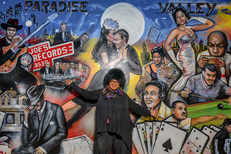 Marsha Music pointing out her father's record store and her father in Curtis Lewis' mural