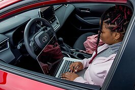 A woman works on a laptop in her car at Ypsilanti Community Middle School, where a new public Wi-Fi hotspot will be located.