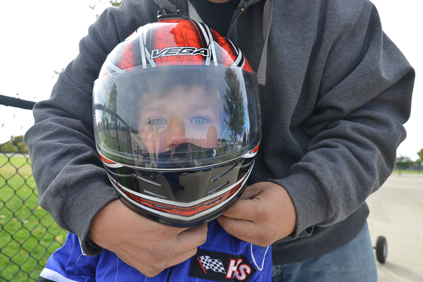 A young racer's father helps him with his helmet